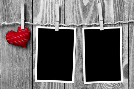 Instant photo frame and love hearts pinned to rope on wooden textured background