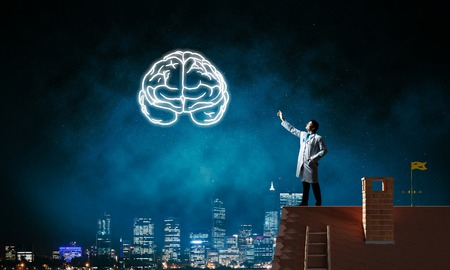 Conceptual image of confident doctor in white uniform interracting with glowing brain symbol while standing on brick roof against night cityscape view on background. Stock Photo