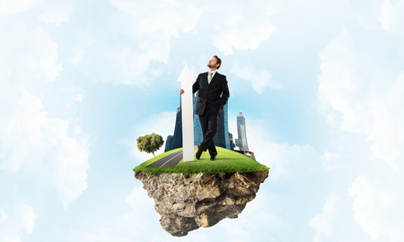 Confident and successful businessman in black suit pointing upside with huge white arrow in his hands while standing on flying island and cloudy skyscape on background. Stock Photo