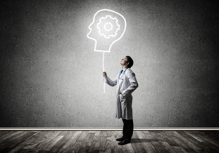 Conceptual image of confident doctor in white uniform interracting with glowing gear brain symbol while standing against gray dark wall on background.