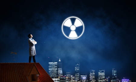 Young medical industry employee standing on brick house roof and interracting with glowing radioactive symbol with night city view on background. Reklamní fotografie