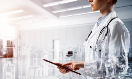 Confident female doctor in white coat using tablet while standing inside hospital office and modern cityscape view on background. Concept of modern technologies for medical industry. Double exposure
