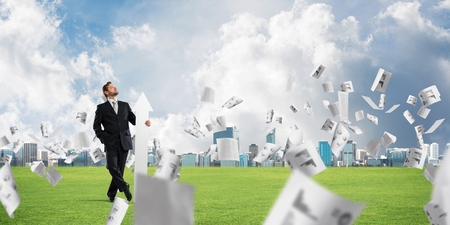 Conceptual image of young businessman in suit looking upside and holding big white arrow in hand while standing among flying papers on green meadow and cityscape view on background.