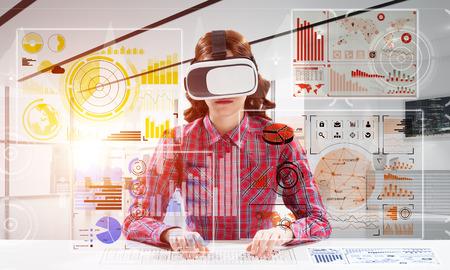 Tecnologías modernas para la educación por medio de una joven estudiante en camisa a cuadros que usa gafas de realidad virtual e interactúa con la interfaz de medios digitales. Foto de archivo