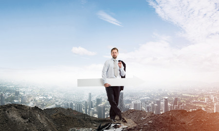 Horizontal shot of young businessman holding white arrow which is pointing sideways while standing against cityscape view and cloudy sky on background. 스톡 콘텐츠