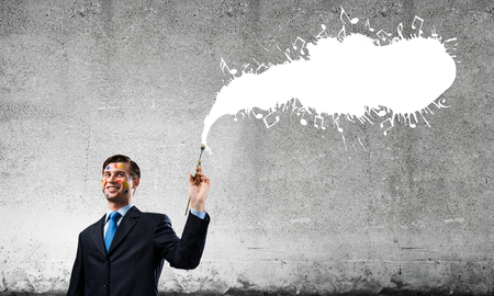 Portrait of young and successful businessman in black suit holding paintbrush in hand while standing with white musical liquid splash and against gray dark background