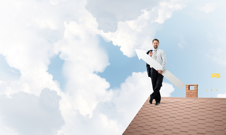 Conceptual image of young businessman in suit showing aside with big white arrow in his hand while standing on the top of brick roof and cloudy skyscape on background. Foto de archivo