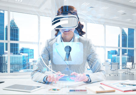 Conceptual image of young successful business woman sitting inside office and using virtual reality headset with security media interface