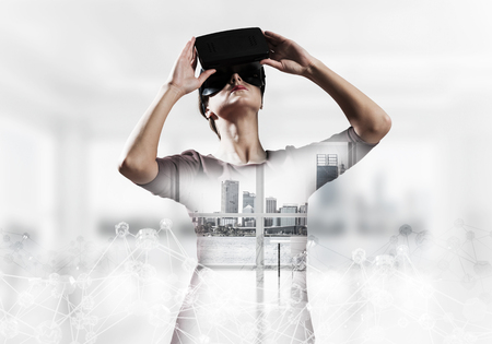 Double exposure of young and beautiful woman in red dress using virtual reality headset while standing indoors of office building with digital network structure.