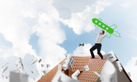 Confident and young businessman in suit starting launching a big rocket from his hand while standing among flying papers on top of brick roof and with cloudy skyscape view on background.