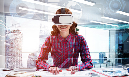 Portrait of beautiful and young woman in red checkered shirt using VR goggles and interracting with digital media interface while sitting inside bright office building. Virtual reality device Stock Photo