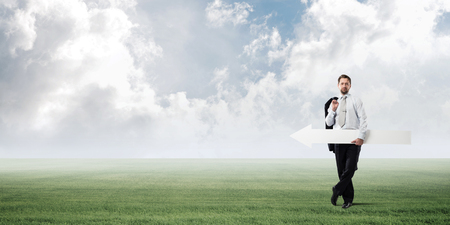 Confident businessman holding jacket behind his back in one hand and white big arrow in another hand while standing at green meadow and skyscape view on background. Foto de archivo