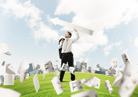 Young and confident businessman in suit starting launching huge white arrow to the air while standing among flying papers on green lawn and cityscape view on background. Stockfoto