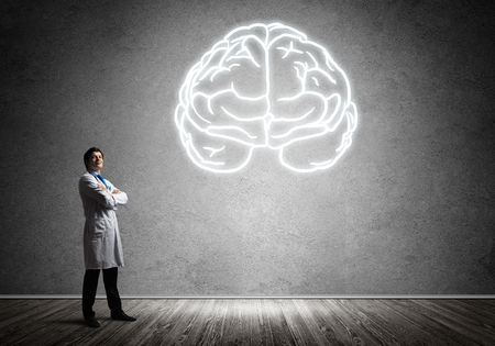 Young and confident doctor in white medical uniform keeping arms crossed and looking at glowing brain symbol while standing against gray wall on background.