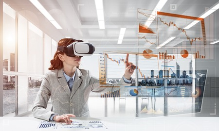 Portrait of confident and successful business woman in suit sitting inside office building with digital media interface and using virtual reality headset