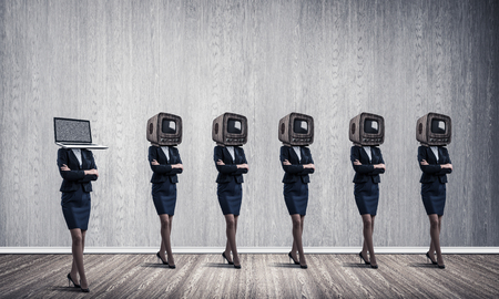 Business women in suits with old TV instead of their heads keeping arms crossed while standing in a row and one at the head with laptop in empty room against gray wall on background.