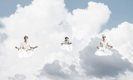 Young family keeping eyes closed and looking concentrated while meditating on clouds in the air with cloudy skyscape on background. Stock Photo