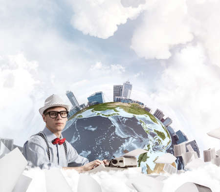 Side view of hard-working man writer using typing machine while sitting at the table with flying papers and Earth globe among cloudy skyscape on background.