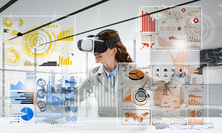 Horizontal shot of young successful business woman sitting inside office and using virtual reality headset with digital media interface Stock Photo - 105500319