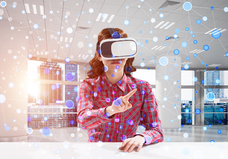 Horizontal shot of young and beautiful woman in checkered shirt using virtual reality headset and media interface while sitting inside bright office building.