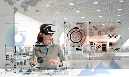 Conceptual image of confident young business woman in suit using virtual reality headset and digital media interface while sitting inside bright office building. Stock Photo - 105673223