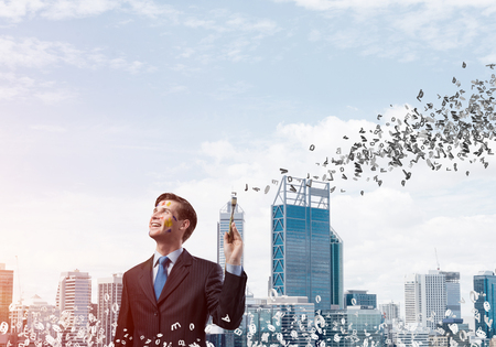 Happy and young businessman in black suit holding paintbrush in his hand and smiling while standing against modern cityscape view on background 스톡 콘텐츠