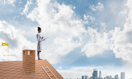 Conceptual image of confident woman doctor in white medical uniform holding notebook in hands while standing on brick roof with cloudy sky and cityscape view on background.