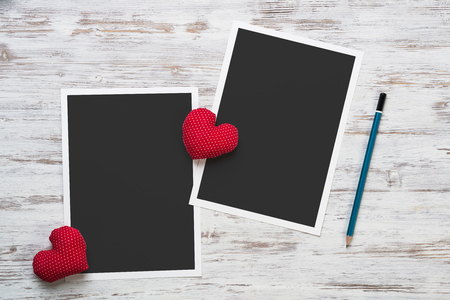 Blank photo frame and love hearts on wooden table Stock Photo