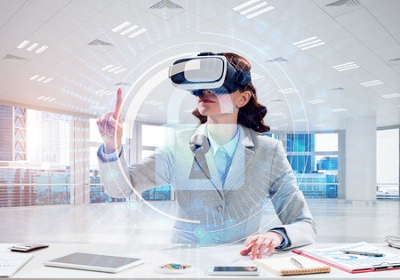 Conceptual image of confident and successful business woman in suit sitting inside office building with security interface and using virtual reality headset Stock Photo - 105861386