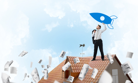 Conceptual image of young confident businessman in suit launching big blue rocket from his hand while standing on the top of brick roof among flying papers with cloudy skyscape view on background.