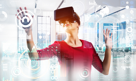 Young and modern business woman in red dress using virtual reality headset while standing inside office building with digital media interface. Stock Photo - 105862514