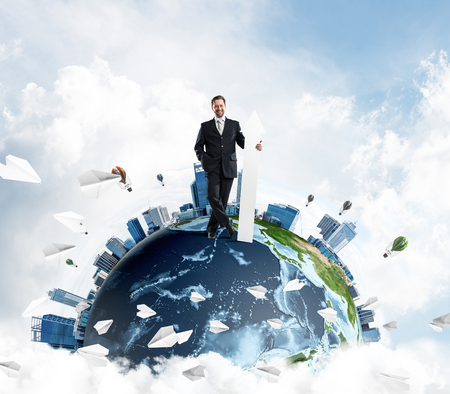 Successful business man in suit holding huge white arrow in hand while standing on Earth globe with cloudy skyscape view on background. Elements of this image are furnished by NASA Foto de archivo