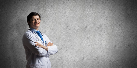 Portrait confident and professional man doctor in white medical suit keeping arms crossed and looking to camera while standing against dark gray wall on background. Medical industry employee concept Banco de Imagens