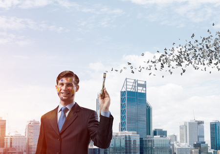 Conceptual image of young and successful businessman in black suit holding paintbrush in hand and smiling while standing against modern cityscape view with flying letters on background.