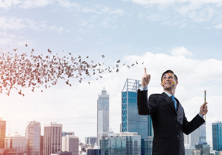 Horizontal shot of cheerful and young businessman in black suit gesturing and smiling while standing against cityscape view with flying letters on background. 스톡 콘텐츠
