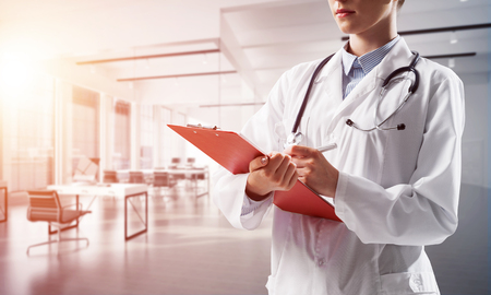 Close up of confident female doctor in white medical uniform making notes into notebook while standing inside of bright hospital building. Medical industry concept