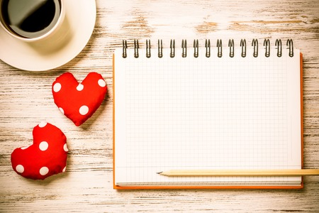 Coffee cup notepad pencil and two red hearts on wooden surface Фото со стока