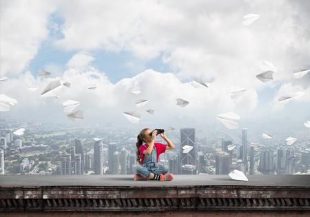 Jolie fille d'âge scolaire sur le toit du bâtiment à la recherche de jumelles