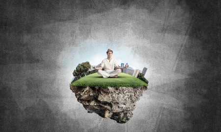 Man in white clothing keeping eyes closed and looking concentrated while meditating on flying island in the air with gray dark wall on background. 3D rendering. Stock Photo