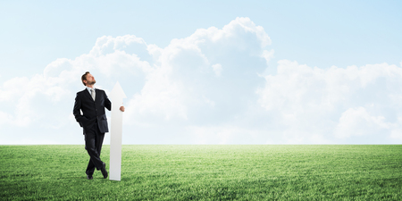 Young businessman in suit looking and pointing upside with big white arrow in hand while standing on green meadow and cloudy skyscape view on background