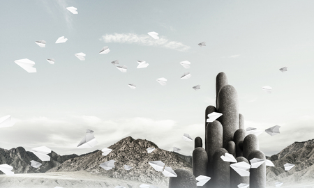 Image of high and huge stone columns located outdoors among flying paper planes with beautiful landscape on background. Wallpaper, backdrop with copyspace. 스톡 콘텐츠
