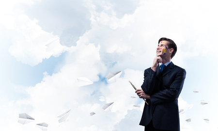 Portrait of confident and young business man holding paintbrush in his hand and looking away while standing against blue cloudy skyscape with flying paper planes on background. 스톡 콘텐츠