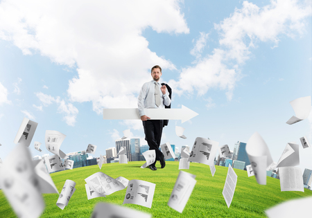 Confident and young businessman in suit holding big white arrow in hands which pointing to the side while standing among flying papers on green lawn and cityscape view on background.