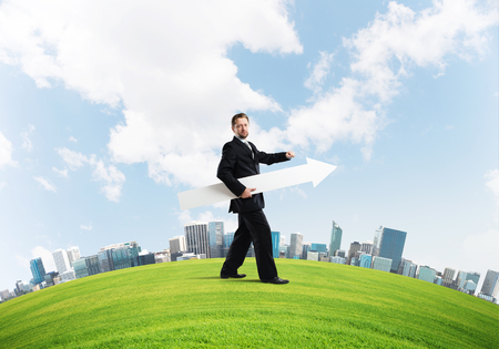 Confident and young businessman in suit holding big white arrow in hands which pointing to the side while standing on green lawn and cityscape view on background.