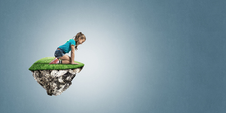 Cute smiling girl sitting on floating island and looking down