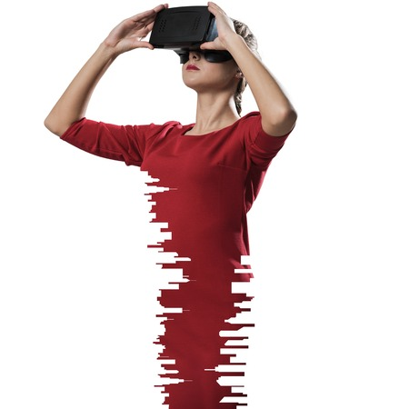 Horizontal shot of young and beautiful woman in red dress using virtual reality headset while standing indoors against white on background