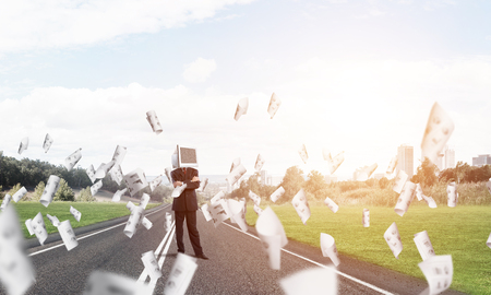 Businessman in suit with monitor instead of head keeping arms crossed while standing on the road among flying papers with beautiful landscape on background. Stock Photo