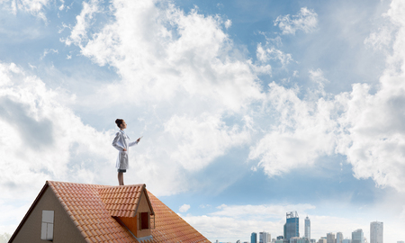 Confident medical industry employee in white suit standing at the top of building roof and holding tablet in hands. Skyscape and city view on background. Medical sphere concept