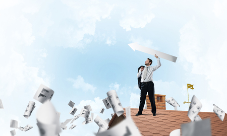 Conceptual image young businessman in suit throwing in air big white arrow while standing on the top of brick roof among flying papers with cloudy skyscape on background.