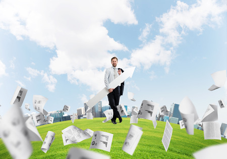 Confident businessman holding jacket behind his back in one hand and white big arrow in another hand while standing among flying papers at green meadow and cityscape view on background.